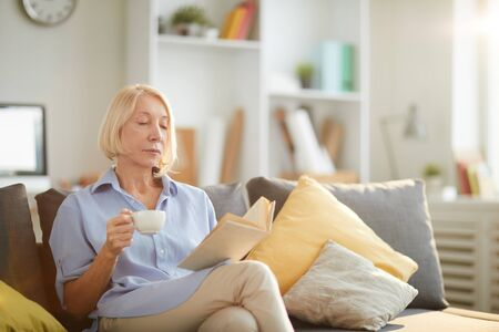 Portrait of contemporary mature woman reading book while relaxing on sofa at home with cup of coffee, copy space