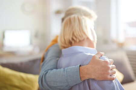 Back view portrait of loving adult couple embracing tenderly, focus on foreground, copy space