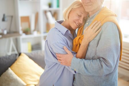 Cropped portrait of loving senior couple embracing tenderly while standing in sunlit living room at home, copy space Standard-Bild - 131098084
