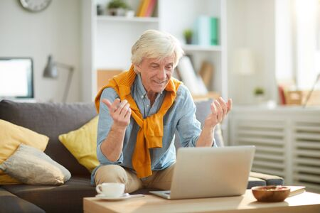 Portrait of emotional senior man using laptop sitting on couch at home and watching sports game or news, copy space Stock Photo