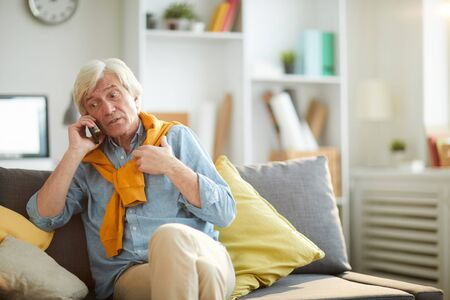 Portrait of modern senior man speaking by smartphone while relaxing sitting on comfortable couch at home, copy space
