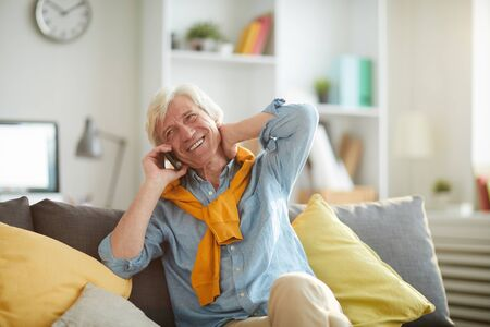 Portrait of smiling senior man speaking by smartphone while relaxing sitting on comfortable couch at home, copy space