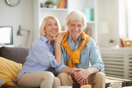 Portrait of happy senior couple looking at camera while embracing lovingly and enjoying weekend at home, copy space