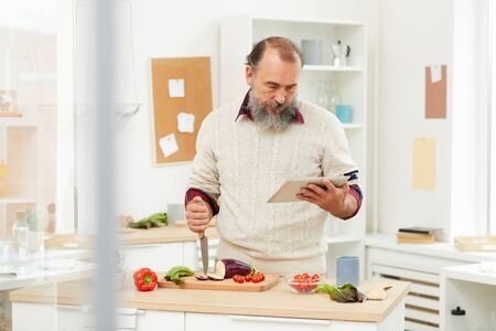 Waist up portrait of bearded senior man looking up recipe via digital tablet while cooking healthy vegetables in kitchen, copy space