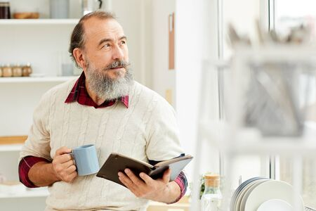 Waist up portrait of bearded senior man looking at window pensively while enjoying cup of coffee in morning and reading book, copy space