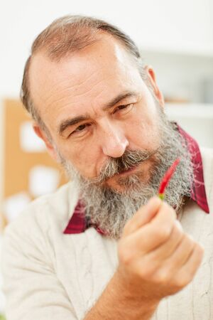 Close up portrait of bearded senior man holding tiny chili pepper and looking at it suspiciously