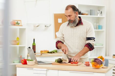 Waist up portrait of bearded senior man watching video recipe via laptop while cooking healthy salad in kitchen, copy space