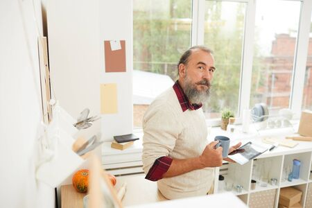 High angle portrait of bearded senior man drinking morning coffee in kitchen and looking up at camera, copy space