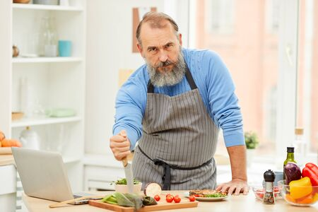 Portrait of tough bearded man holding knife and looking at camera while cooking meat in kitchen, copy space Stock Photo