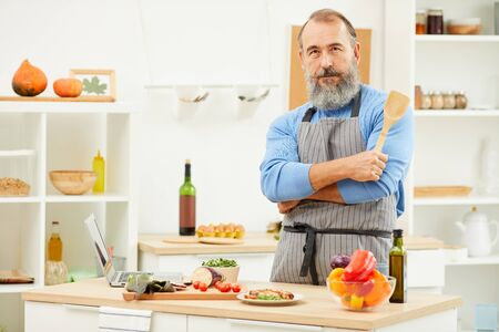 Waist up portrait of bearded senior man cooking at home and looking at camera while posing confidently in kitchen, copy space