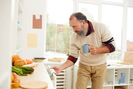 Side view portrait of bearded senior man opening kitchen cupboards while looking for breakfast in morning, copy space