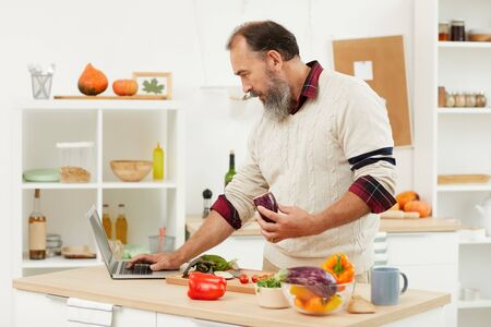 Waist up portrait of bearded man watching video recipe via laptop while cooking healthy food in kitchen, copy space