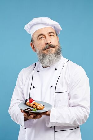 Waist up portrait of cheerful senior chef presenting beautiful dessert while standing against blue background Stock Photo