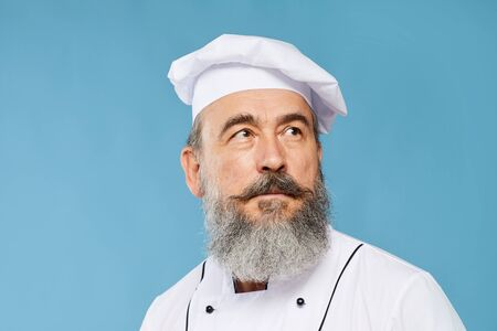 Head and shoulders portrait of charismatic bearded chef looking up while posing standing against blue background, copy space Stock Photo