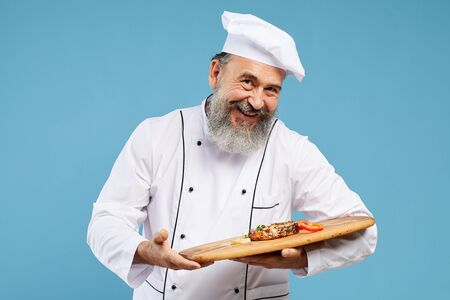 Waist up portrait of cheerful senior chef holding beautiful dish on wooden platter while standing against blue background and looking at camera, copy space Stock Photo