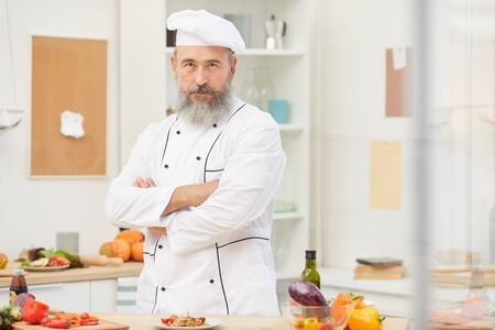 Waist up portrait of bearded senior chef posing confidently while standing in restaurant kitchen, copy space