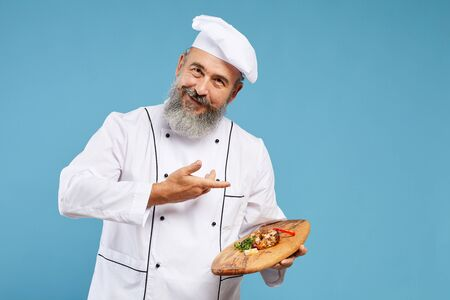 Waist up portrait of cheerful senior chef presenting beautiful dish on wooden platter while standing against blue background and smiling at camera