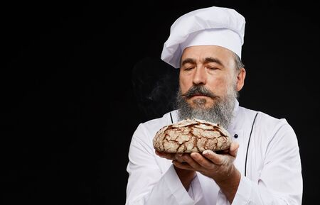 Portrait of charismatic bearded baker holding fresh bread loaf lovingly while standing against black background, copy space Standard-Bild