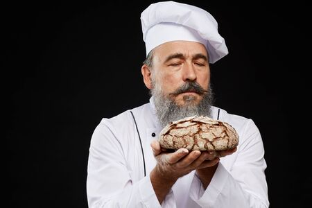 Waist up portrait of charismatic bearded baker holding fresh bread loaf lovingly while standing against black background, copy space Stockfoto