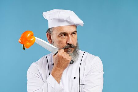 Portrait of pensive bearded chef holding sharp knife with bell pepper pierced on it while posing against blue background in studio, copy space