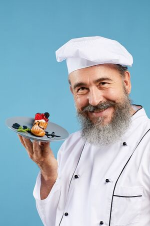 Portrait of cheerful senior chef presenting beautiful dessert while standing against blue background and smiling at camera Stock Photo