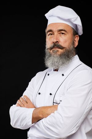 Professional waist up portrait of bearded senior chef posing against black background standing with arms crossed Фото со стока