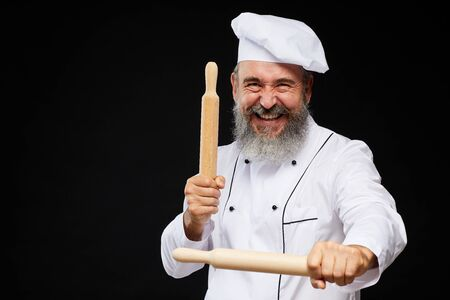 Waist up portrait of cheerful bearded baker holding two rolling pins while standing against black background and laughing, copy space Reklamní fotografie