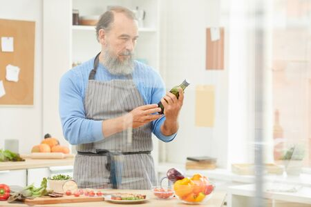 Waist up portrait of bearded senior man cooking dinner at home and reading nutrition label on olive oil, copy space