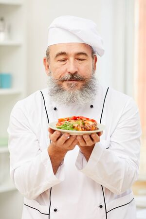 Portrait of bearded senior chef holding delicious meat steak while standing in restaurant kitchen, copy space Stock Photo