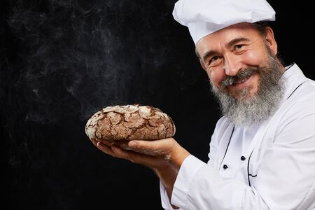 Portrait of charismatic bearded baker holding fresh bread loaf while posing against black background and smiling at camera, copy space