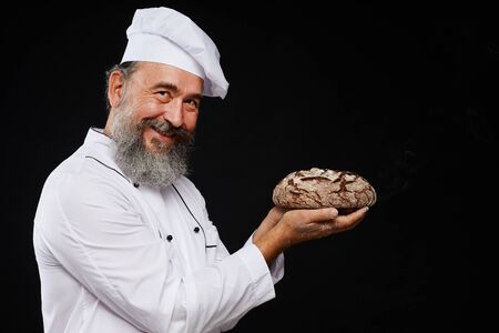 Side view portrait of charismatic bearded baker holding fresh bread loaf while standing against black background and smiling at camera, copy space