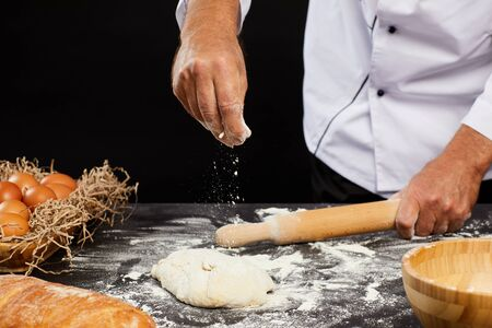 Closeup of unrecognizable baker sprinkling flour on puffy batter while making traditional bread against black background, copy space Фото со стока