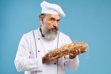 Waist up portrait of charismatic bearded chef holding fresh eggs while posing against blue background and looking at camera, copy space
