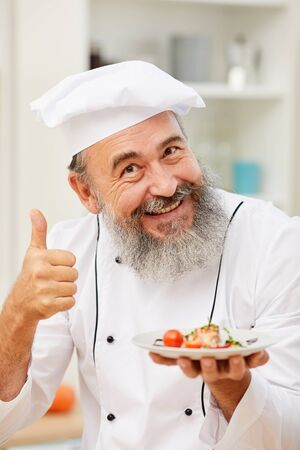 Portrait of cheerful senior chef presenting beautiful Italian dish and showing thumbs up while posing in restaurant kitchen