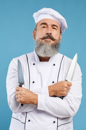 Waist up portrait of charismatic bearded chef looking at camera holding two knives while standing against blue background
