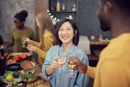 Waist up portrait of smiling Asian young woman clinking glasses with friend while enjoying party in modern interior, copy space