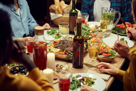 Close up of unrecognizable people enjoying dinner together, focus on delicious homemade food and wine set on wooden table, copy space