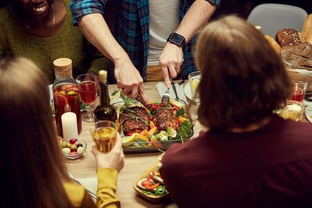 Close up of unrecognizable people enjoying dinner together, focus on man cutting delicious meat loaf set on wooden table, copy space