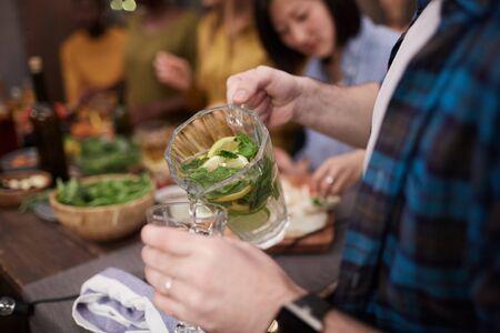 Primer plano de un joven irreconocible vertiendo refrescante limonada en vaso mientras disfruta de la fiesta de verano con amigos, espacio de copia Foto de archivo