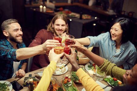 High angle view at multi-ethnic group of people raising glasses and toasting in celebration sitting at dinner table in dimly lit room, copy space