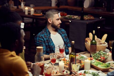 Portrait of bearded young man playing guessing game with friends during dinner party, copy space