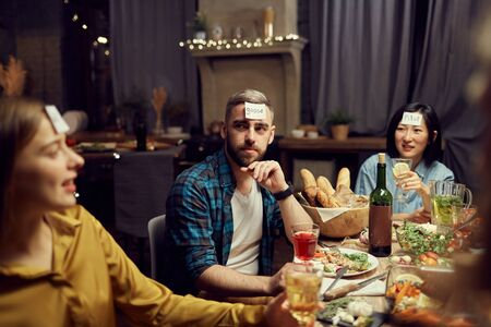 Group of people playing guessing game while sitting at table enjoying dinner party in dark room, copy space Imagens