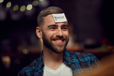 Head and shoulders portrait of smiling bearded man with goose label on forehead playing guessing game with friends during party Imagens