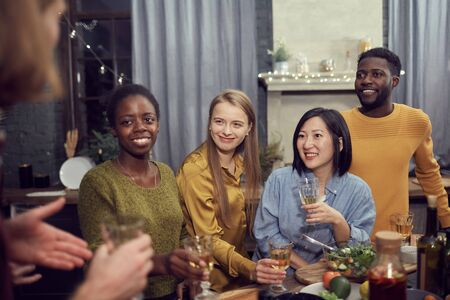 Multi-ethnic group of young people enjoying party standing at table in modern interior and listening to friend telling story