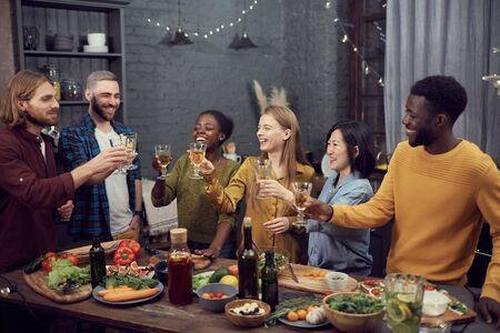Multi-ethnic group of smiling young people enjoying dinner together standing at table in modern interior and toasting with wine glasses, copy space