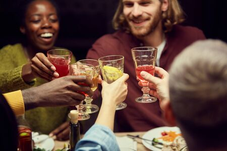 Cropped photo of young friends clinking glasses with colorful alcohol while enjoying party in dark room, copy space Imagens