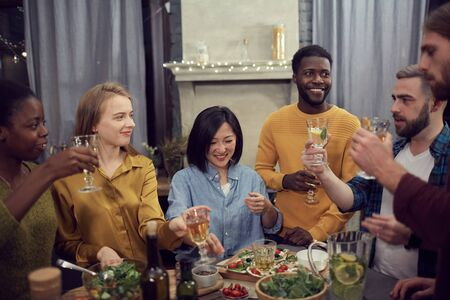 Multi-ethnic group of young people enjoying dinner together standing at table in modern interior and holding wine glasses