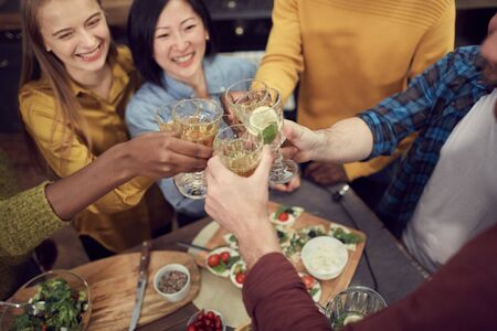 High angle portrait of friends toasting in celebration holding glasses with wine and lemonade over dinner table during party, copy space