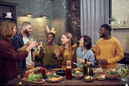 Multi-ethnic group of smiling young people enjoying dinner together standing at table in modern interior and holding wine glasses, copy space Imagens