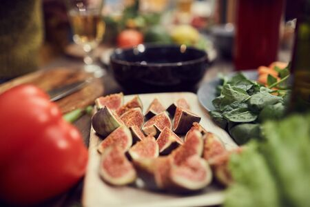 Close up of exotic passion fruit snack on wooden plate surrounded with healthy dinner foods, copy space